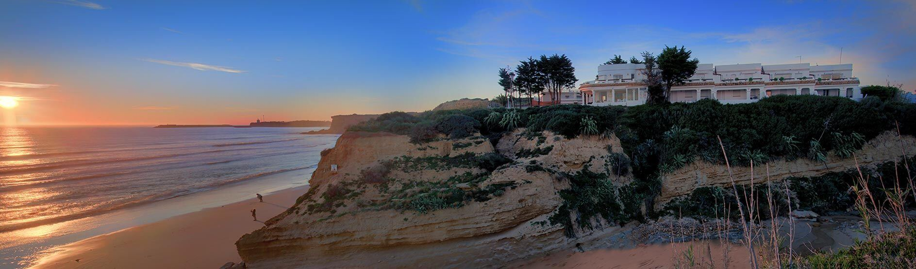 View of the cliff and the sea with the lighthouse of Conil in the background - Accommodation Flamenco Villas in Conil